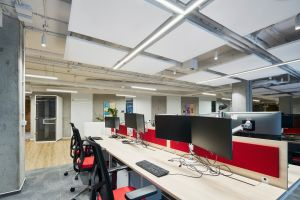 Nad biurkami zwisły struktury akustyczne i dostosowane oświetlenie, które zapewniają pracownikom open space doskonałe warunki do pracy, dają poczucie przestrzeni i stymulują ich kreatywność. Projekt: The Design Group. Fot. mat. prasowe Rockfon