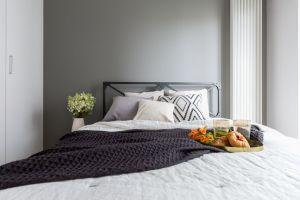 Sypialnia zdecydowanie nawiązuje do klimatu industrialnego – szara ściana i metalowa rama łóżka korespondują z resztą wnętrza, jednocześnie nadając tej części mieszkania bardziej klasyczny, surowy ton. Projekt i zdjęcia: Decoroom