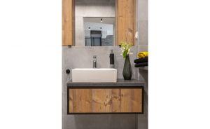 W aranżacji łazienki wykorzystano betonowy gres z delikatnym wzorem i metalowe ramy – na lustrze, szafce umywalkowej oraz prysznicu. Projekt i zdjęcia: Decoroom