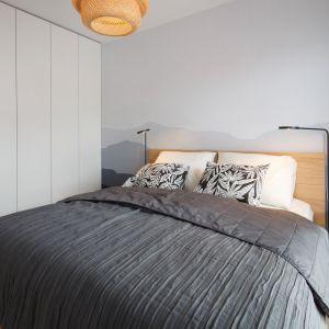 Dominującym elementem niewielkiej sypialni jest wygodne łóżko, wykończone jasnym, drewnianym fornirem. Projekt: Czajkowski Kluźniak Architekci. Fot. Archifolio / Tomasz Zakrzewski