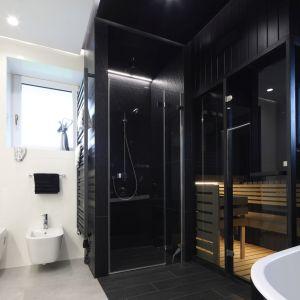 Inwestorom zależało, aby w ich domowej łazience znalazło się też miejsce na saunę. Znalezienie firmy, która podjęłaby się wykonania sauny w harmonizującym z resztą wystroju, czarnym kolorze, okazało się sporym wyzwaniem. Projekt: arch. Dariusz Grabowski. Fot. Bartosz Jarosz