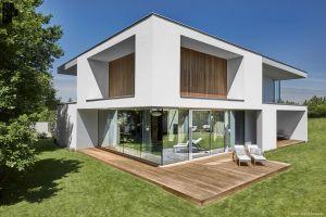 Dom składa się z dwóch brył – białej, dla której charakterystyczne są płaskie elewacje, obłożone elementami drewna oraz szarej, cofniętej względem białej. Projekt: 81.WAW.PL. Fot. Bartek Zaranek