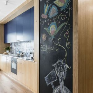 Wysoka zabudowa kuchenna w dębowym wykończeniu jest wizualną kontynuacją mebli z przedpokoju.