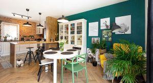 W mieszkaniu dominuje neutralna kolorystka, przełamana kontrastami w postaci ciemnozielonej ściany, żółtego fotela i biało-czarnej podłogi w strefie kuchennej. Całość tchnie bardzo naturalną, domową atmosferą.