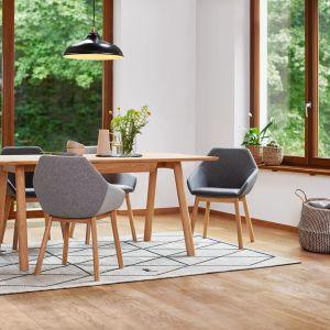 Nowoczesne i ergonomiczne krzesła Tuk z tapicerowanym siedziskiem i oparciem na drewnianych nogach. Fot. Paged Meble