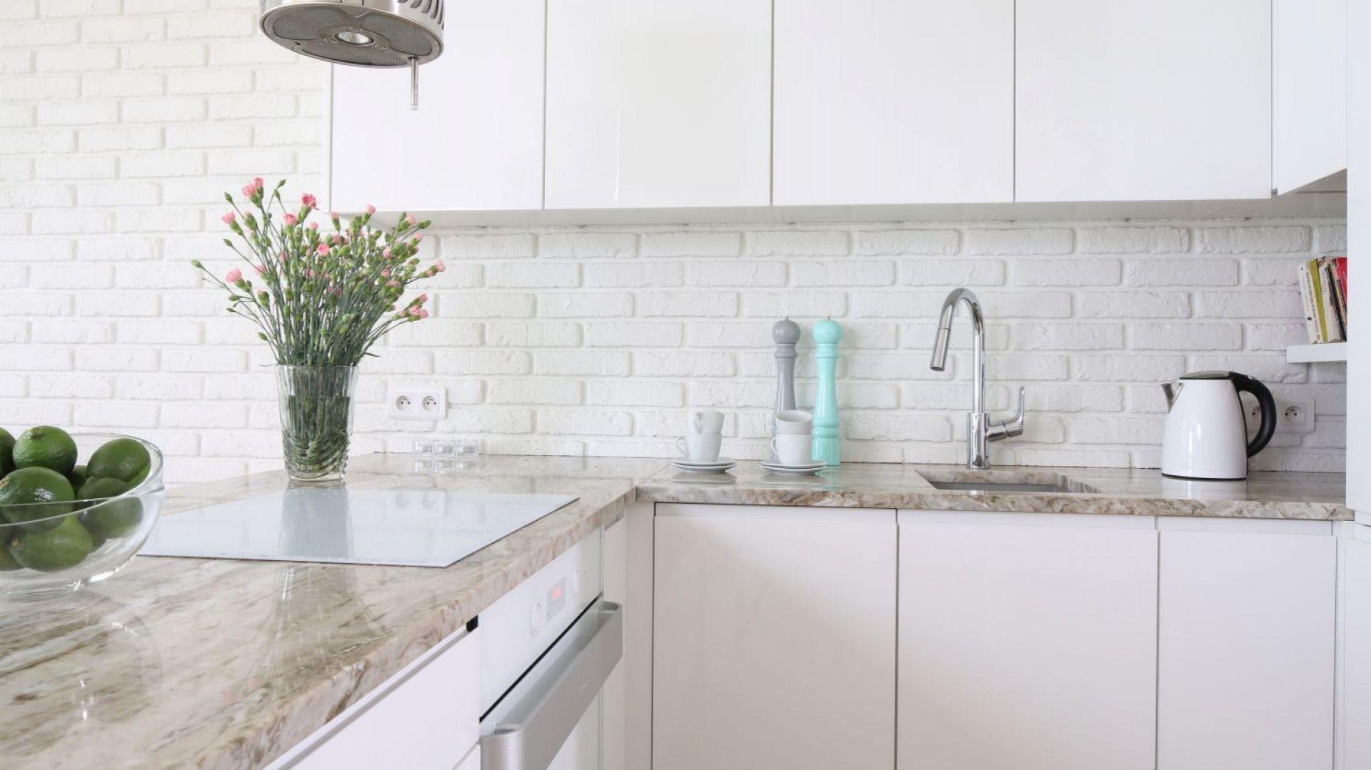 Do nowoczesnej kuchni z minimalistyczną zabudową zaproszono także cegłę, która stanowi akcent loftowy oraz kamień naturalny typowy dla klasycznych wnętrz. Projekt: Laura Sulzik. Fot. Bartosz Jarosz