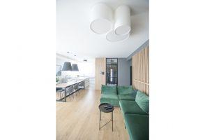 Oryginalne elementy dekoracyjne, takie jak np. drewniane lamele na ścianie w pokoju dziennym, czy przykuwająca wzrok tapeta w geometryczny wzór w sypialni, nie przytłaczają przestrzeni. Projekt i zdjęcia: mia architekci