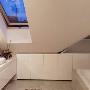 Z pokojami na piętrze sąsiaduje przestronna łazienka, doświetlona dwoma oknami dachowymi. W łazience również Architekt postawiła na biel oraz jasne drewno. Fot. Studio BB Architekci