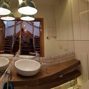 Na parterze znajduje się także niewielka łazienka dla gości o mozaikowych płytkach na podłodze. Do wysokości lustra ściana pokryta jest cegłą pomalowaną na biało. W pomieszczeniu znajduje się również industrialna lampa o zielonym kolorze. Fot. Studio BB Architekci