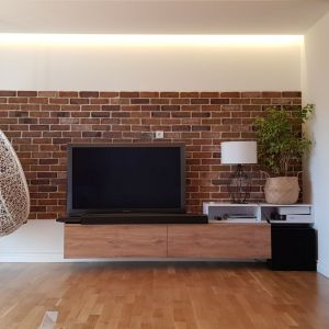 Strefa telewizyjna to ściana z ceglanym fragmentem, wiszący fotel, podwieszana drewniana szafka. Fot. Studio BB Architekci