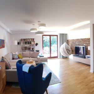 Wnętrze nowoczesnego salonu wypełniają duża kanapa w kształcie litery C, granatowy fotel, poziomy obraz, białe, wiszące półki, wiszące okrągłe lampy. Fot. Studio BB Architekci