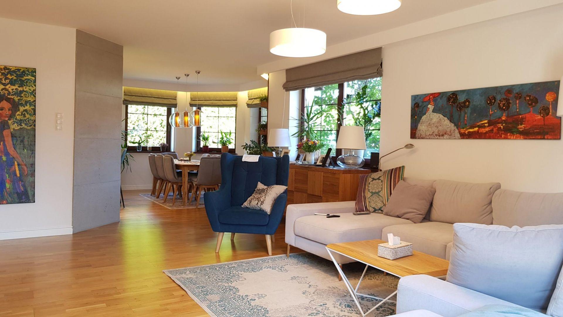 Białe ściany pomieszczenia ubogaca obraz oraz nieregularny regał. Wisienkę na torcie stanowią wzorzyste poduszki oraz dywany. Fot. Studio BB Architekci