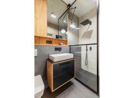 Ścianka wydzielająca prysznic w łazience nawiązuje do konstrukcji pomiędzy kuchnią a salonem. Projekt i zdjęcia: Deer Design