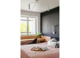 Wykonana na wymiar zabudowa ściany za łóżkiem płynnie przechodzi w biurko, tworząc wygodne miejsce do pracy przy oknie. Projekt i zdjęcia: Deer Design