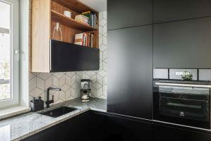 Minimalistyczna forma czarnej zabudowy i lekkie dodatki nie przytłaczają wnętrza. Projekt i zdjęcia: Deer Design