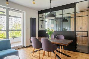 W rezultacie powstało piękne mieszkanie, w którym proste formy, geometryczne wzory, czarne dodatki i drewno wzajemnie się przeplatają, tworząc harmonijną kompozycję. Projekt i zdjęcia: Deer Design