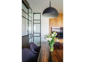 Kuchnia została nietypowo oddzielona od salonu i jadalni szklaną ścianką z czarnymi szprosami. Projekt i zdjęcia: Deer Design