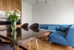 Na tle neutralnych białych ścian części dziennej pięknie wyeksponowano stół. Projekt i zdjęcia: Deer Design