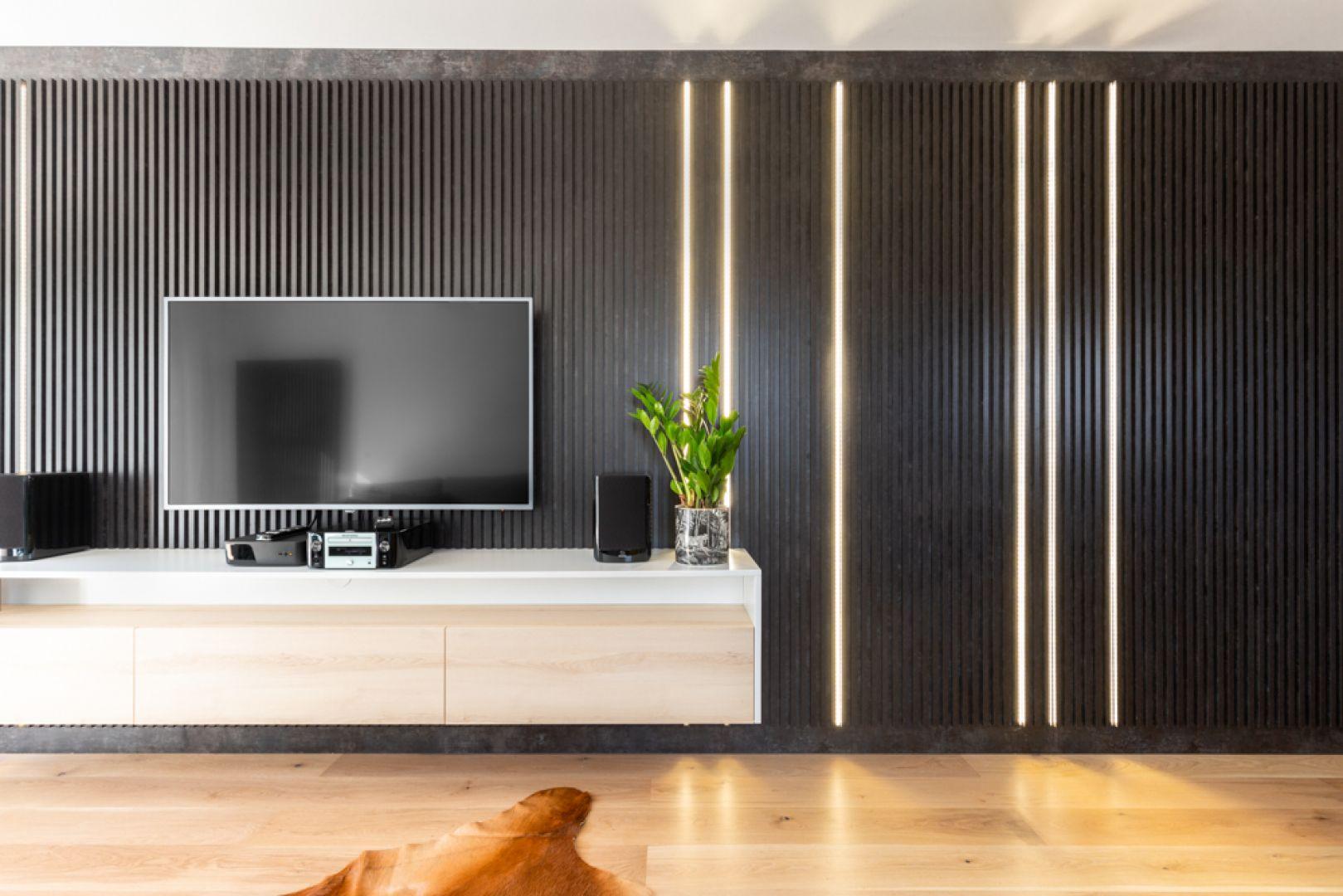 Ścianę za szafką RTV zdobi oryginalna czarna zabudowa z ledowym podświetleniem. Projekt: Joanna Rej. Realizacja: Gama Design. Fot. Pion Poziom