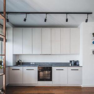 Zabudowa w kuchni została również utrzymana w bieli, dzięki czemu niemal wtapia się w ścianę. Projekt: Taff Architekci. Fot. Ignacy Matuszewski