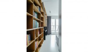 Zabudowa ściany z telewizorem ma swoją kontynuację w postaci pojemnej, nieszablonowej biblioteczki, ulokowanej w gabinecie
