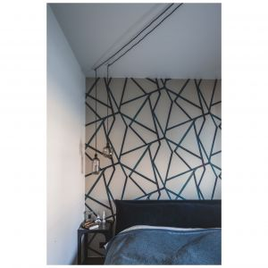 Sypialnia jest kontynuacją całego projektu. Tu również królują proste formy i designerskie dodatki. W roli głównej tapeta z niebieskim, geometrycznym wzorem. Projekt: Taff Architekci. Fot. Ignacy Matuszewski