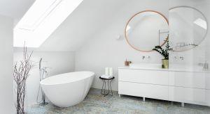 Wpadające do wnętrz przez okazałe okno połaciowe światło odbija się od śnieżnobiałych ścian i sufitu, rozświetlając tę przestronną łazienkę urządzoną w konwencji salonu kąpielowego. Wnętrze sprawia wrażenie wypełnionego świeżym po