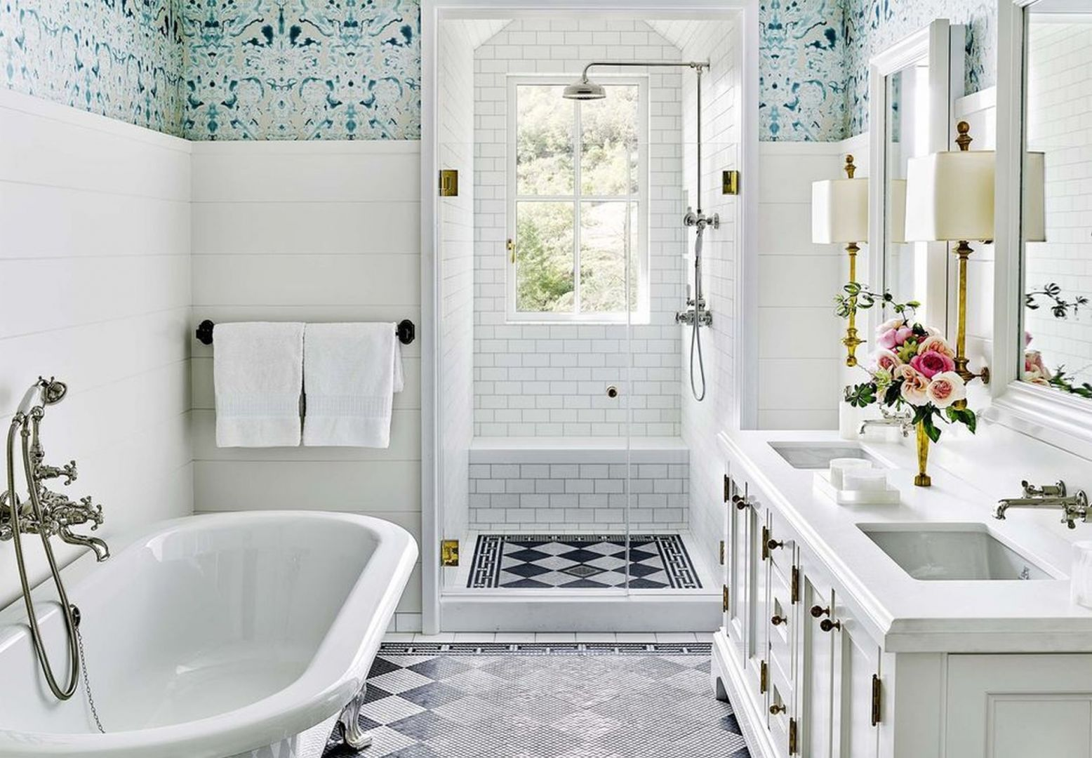 Wąska łazienka jest optyczni powiększona dzięki  wzorowi płytek który został celowo rozciągnięty na strefę prysznica, a zastosowanie prostych i wąskich meblami, dają uczucie że łazienka jest większa niż w rzeczywistości. Fot. Douglas Friedman