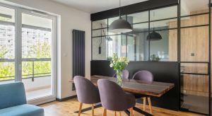W tym warszawskim mieszkaniuproste formy, geometryczne wzory, czarne dodatki i drewno wzajemnie się przeplatają, tworząc spójną i harmonijną kompozycję.