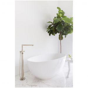 W tej łazience projektant przyjął ultra-minimalistyczne podejście  w aranżacji opartej na prostych  liniach geometrii. Dominuje tu czysta biel, a akcentem kolorystycznym jest roślina doniczkowa, dzięki czemu przestrzeń wydaje się otwarta i funkcjonalna. Fot. Alyssa Rosenheck