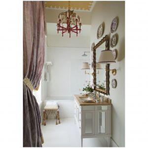 Wąska łazienka z lustrem z lat 40-tych i stołkiem z Newel z lat 50-tych XX w. została udekorowana zdobionym lustrem z lat 40-tych i stołkiem z lat 50-tych. Żyrandol  z lat 70-tych pochodzi z  Palm Beach, zasłony wykonane są z jedwabiu przez Manuela Canovasa, a umywalka, wanna i armatura łazienkowa z firmy Villeroy & Boch. Fot. Fritz von der Schulenburg