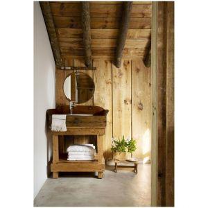 W małym wypoczynkowym domu w Portugalii, umywalka została wykonana przez lokalnego rzemieślnika, a armatura została jest od firmy  Grohe. Lustro zostało zakupione w IKEA, a podłoga jest betonowa. Całość ociepla drewno. Fot. Ricardo Labougle
