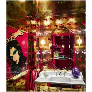 Jak na małą przestrzeń, łazienka Andy'ego Cohena wygląda całkiem przestronnie. Ściany wyłożone są tapetą Cherry Forever Flavor Paper's Cherry Forever, umywalka z konsolą autorstwa firmy Waterworks, a zabytkowe lustro Milo Baughman zostało wykonane z krzesła. Nad pokojem znajduje się portret Andy'ego Warhola, przedstawiający Diane von Furstenburg w jedwabnej chuście. Fot. Douglas Friedman