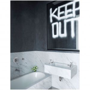 Wanna i armatura umywalkowa w łazience gościnnej projektantów Kevina Robertsa i Timothy'ego Haynesa są wykonane przez firmę Barbera Wilsonsa & Co., na lustrze napis autorstwa Rashida Johnsona. Fot. Simon Upton