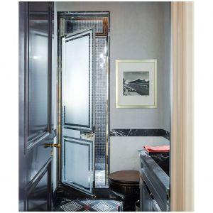 Metaliczno-marmurowe drzwi prysznicowe i strefa umywalki w tym zaprojektowanym przez Stevena Gambrela domu na Manhattanie są projektowane na zamówienie, a podłogi i płytki autorstwa Mosaic House. Fot. Cynthia Frank