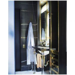 W tym apartamencie na Manhattanie, wykończenia z mosiądzu podkreślają męski charakter łazienki. Umywalka autorstwa Urban Archeology  a armatura została wykonana przez Waterworks. Ściany są pokryte marmurem Saint Laurent. Fot. Simon Upton
