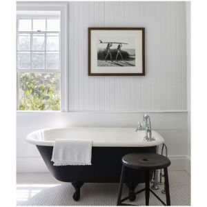 Ta mała, gościnna łaźnia w domku letniskowym Hamptons jest zorganizowana wokół oryginalnej wannie wolnostojącej i armaturą z firmy Waterworks. Stołek to dzieło sztuki i jest autorstwa Michaela Dwecka. Fot. Bjorn Wallander