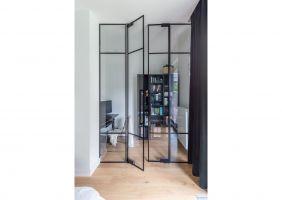 """Ciekawym elementem w sypialni są także metalowe drzwi z przeszkleniami, za którymi """"ukryto"""" mały gabinet do pracy wstępnie przeznaczony na garderobę. Projekt i zdjęcia: Decoroom"""