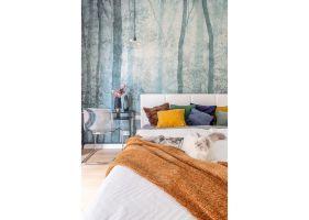 Utrzymany w niebieskościach i zieleni motyw drzew idealnie komponuje się z żółtymi i musztardowymi poduszkami oraz pledem w kolorze ciepłego brązu, który zachęca do otulenia się i odpoczynku. Projekt i zdjęcia: Decoroom