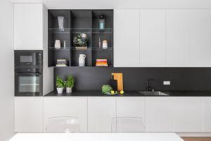 Znajdziemy tu niestandardowo dużo miejsca do przechowywania: sporą liczbę dobrze rozplanowanych szafek i szuflad oraz pokaźny blat roboczy, który docenią nie tylko domowi kucharze. Projekt i zdjęcia: Decoroom