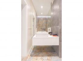 Lustra zamontowane na całej ścianie za umywalką i dekoracyjność sprowadzona do dyskretnych elementów, jak np. ozdobne płytki Aparici Carpet na podłodze, to elementy wspólne dla obu łazienek, budujące spójny klimat. Projekt i zdjęcia: Decoroom