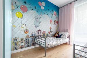 W dwóch niestandardowo wyposażonych pokojach dziecięcych pojawia się szersza paleta barw. Jedno z pomieszczeń jest bowiem sypialnią, w której na jednej ze ścian króluje urocza tapeta z bajkowym motywem a drugie przeznaczono na miejsce do zabawy. Projekt i zdjęcia: Decoroom