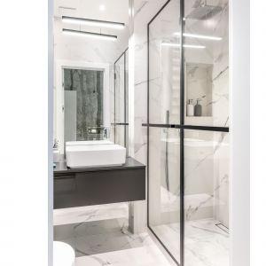 Maksymalny komfort uzyskano za pomocą prysznica typu walk in z odpływem liniowym, deszczownicą podtynkową, a całość dopełniają stylowe drzwi do prysznica w metalowych ramach. Projekt i zdjęcia: Decoroom