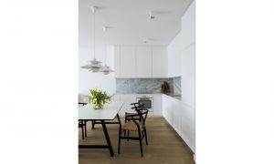 Lokatorzy zdecydowali się na nowoczesne połączenie kuchni z pokojem dziennym. Otwarcie wnętrza oraz zastosowanie bieli optycznie powiększyło przestrzeń. Co więcej, monochromatyczna zabudowa kuchenna w duecie z marmurem na ścianie nadaje pomieszczeniu klasy. Projekt: Madama. Fot. Yassen Hristov