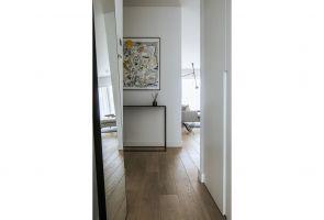 Wizytówkę mieszkania stanowi korytarz, utrzymany w stylistyce, będącej połączeniem klasycznej bieli z drewnem i czarnym dodatkiem w postaci nowoczesnego stolika. Minimalistyczne lustro zostało nonszalancko oparte o ścianę. Projekt: Madama. Fot. Yassen Hristov