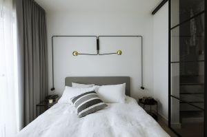 Sypialnia stanowi kontynuację minimalistycznego projektu – królują tu proste formy, biele i szarości. Główną rolę odgrywa nowoczesne oświetlenie Ultralight, ulokowane nad łóżkiem. Projekt: Madama. Fot. Yassen Hristov