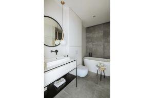 W łazience również zdecydowano się na klasyczną biel z czarnymi dodatkami. Aby dodać jej charakteru, zestawiono ją jednak z powierzchnią imitującą beton – na ścianie oraz podłodze. Projekt: Madama. Fot. Yassen Hristov