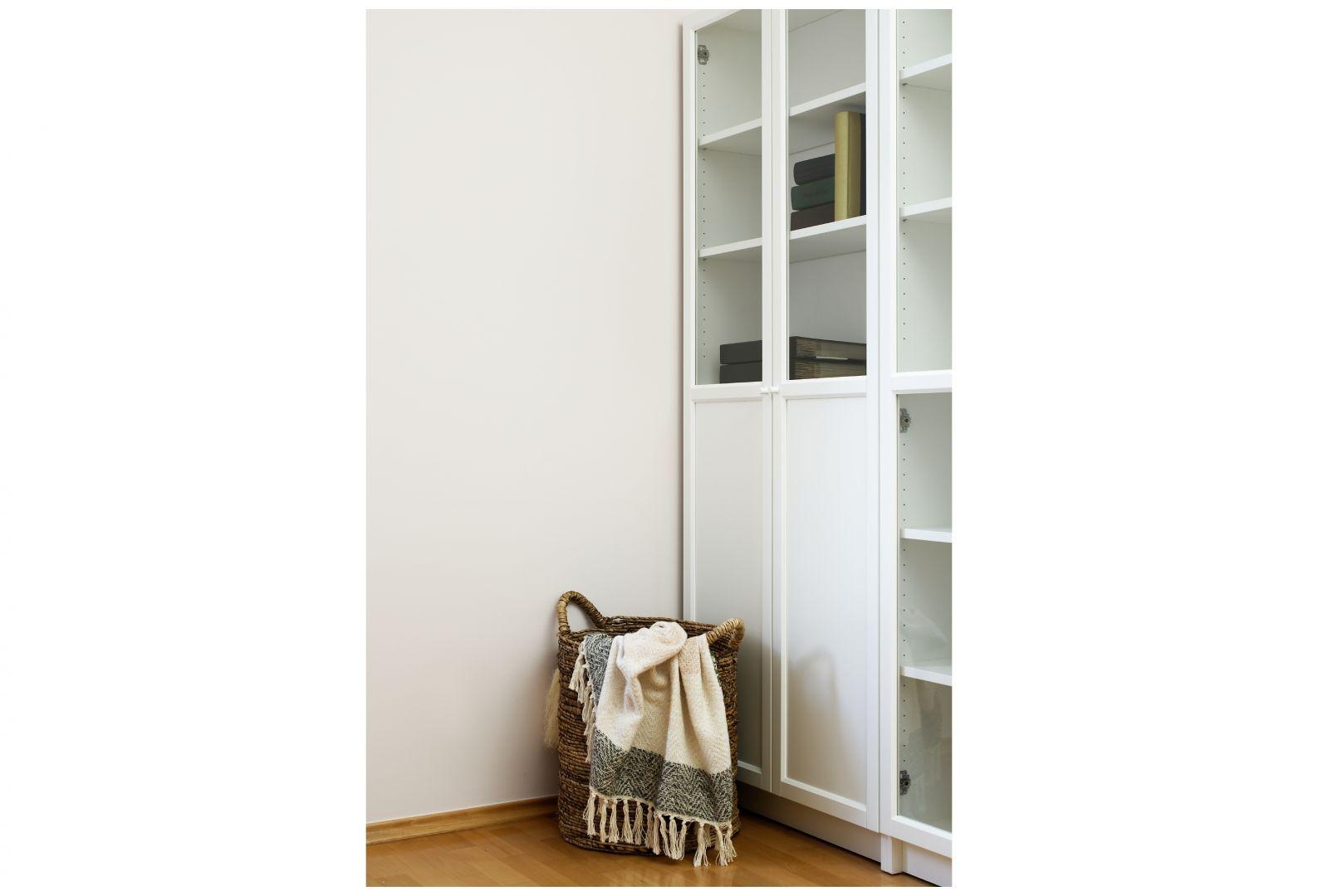 Garderobę w sypialni stanowi  biała szafa z gustownymi uchwytami, natomiast akcesoria i dodatki zostały umieszczone w częściowo oszklonych regałach. Projekt: Aleksandra Sowińska. Fot. Radek Słowik