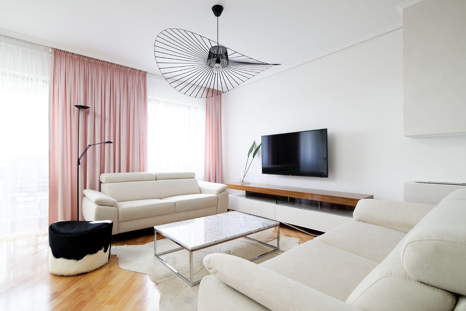 Nowoczesna szafka pod telewizor Rimini Premium firmy Lissy stanowi połączenie stali nierdzewnej, białych frontów oraz lakierowanego drewnianego blatu, który nadaje pomieszczeniu szlachetnego charakter. Projekt: Aleksandra Sowińska. Fot. Radek Słowik