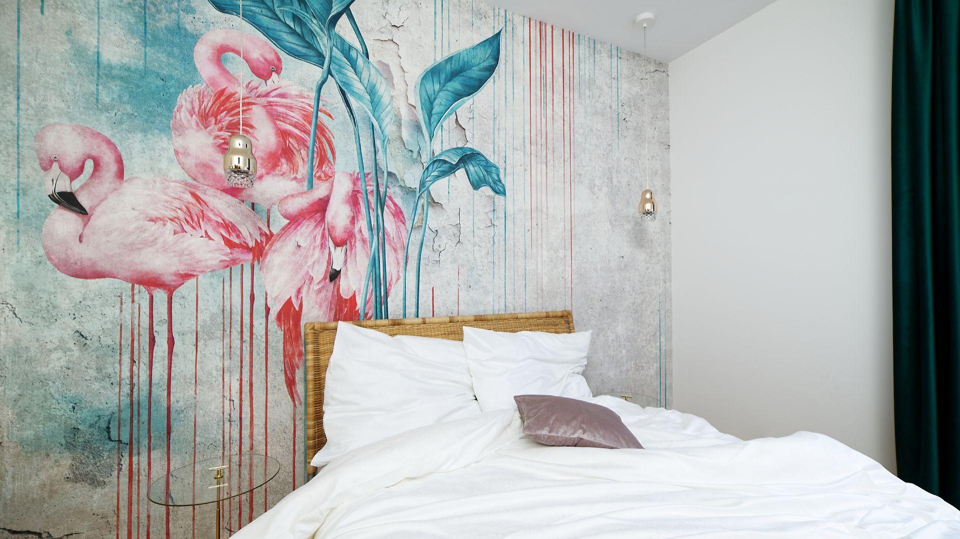 W sypialni ustawiono piękne rattanowe łóżko oraz komodę, do koloru której nawiązują wiszące, złote lampki nocne ze szklanym kryształowym kloszem. Projekt: Aleksandra Sowińska. Fot. Radek Słowik